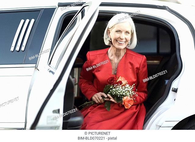 Well dressed senior woman sitting limousine with flowers