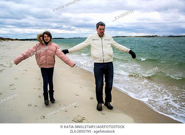 Father playing with his daughter and playing in the wind on the beach and letting themselves flow
