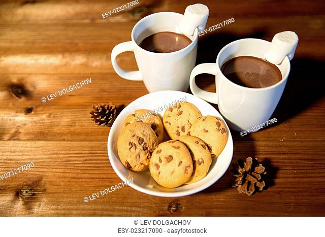 holidays, christmas, winter, food and drinks concept - close up of cups with hot chocolate or cocoa drinks and marshmallow with oat cookies on wooden table