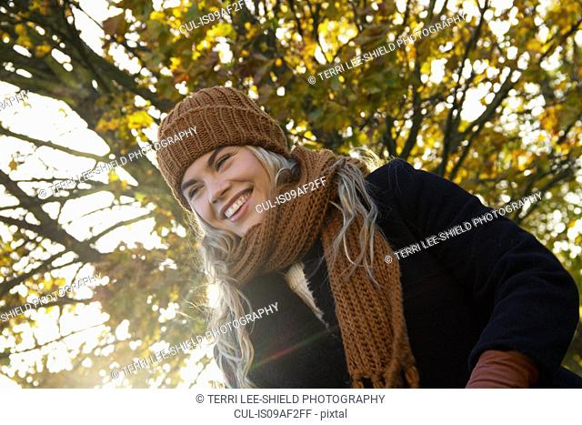 Smiling young woman wrapped up in autumnal park