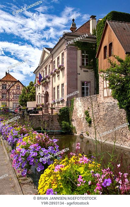 Flowers line the walkway to the Hotel de Ville (Marie) and the medieval town of Riquewihr, Alsace, France