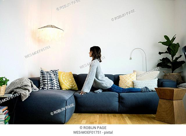 Mature woman practising pidgeon pose on her couch
