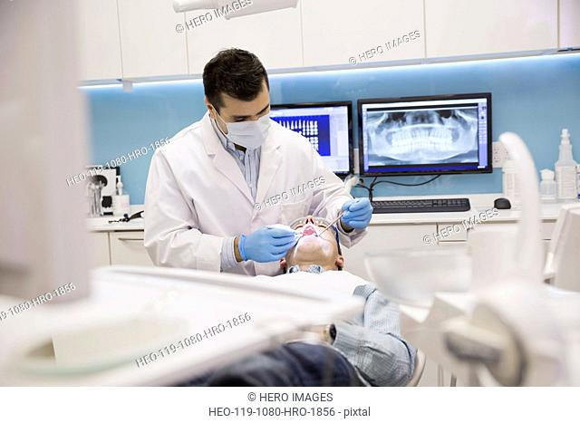 Dentist in surgical mask examining patients mouth
