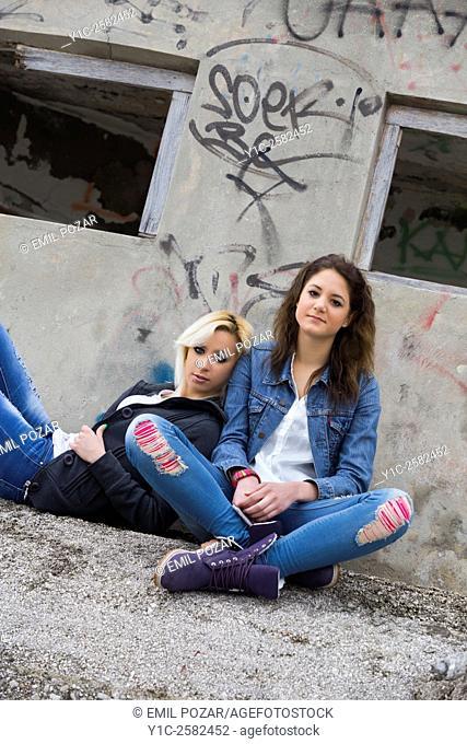 Teen girlfriends sitting on street