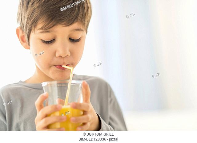 Hispanic boy drinking juice with straw