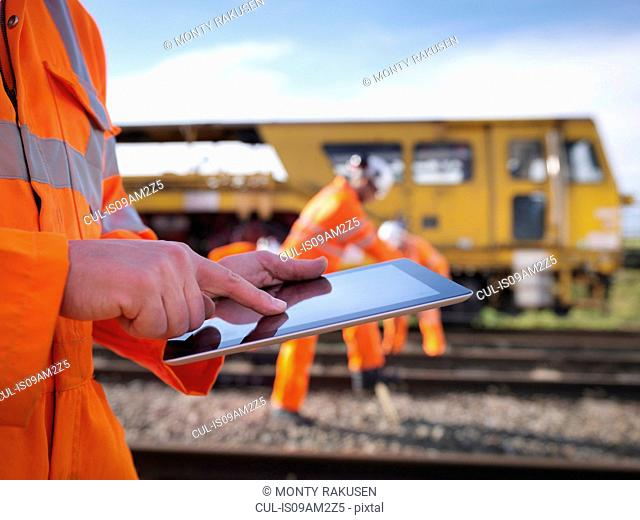 Railway maintenance worker using digital tablet, close up