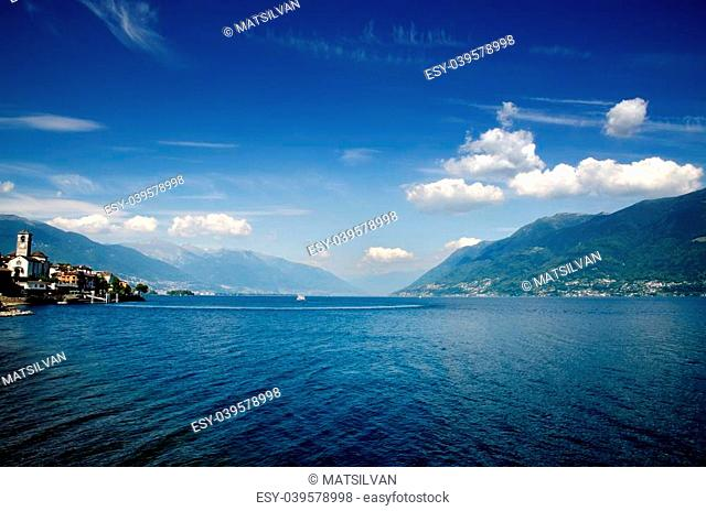 Lake with mountains and blue sky with clouds in brissago ticino switzerland