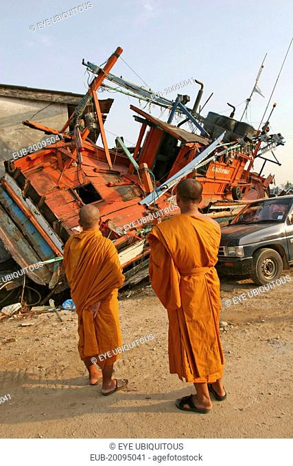 Tsunami. Monks looks at the damage caused by the tsunami, nothing is left standing in the village 2500 people are pressumed dead