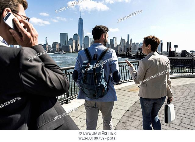 USA, colleagues walking at New Jersey waterfront with view to Manhattan