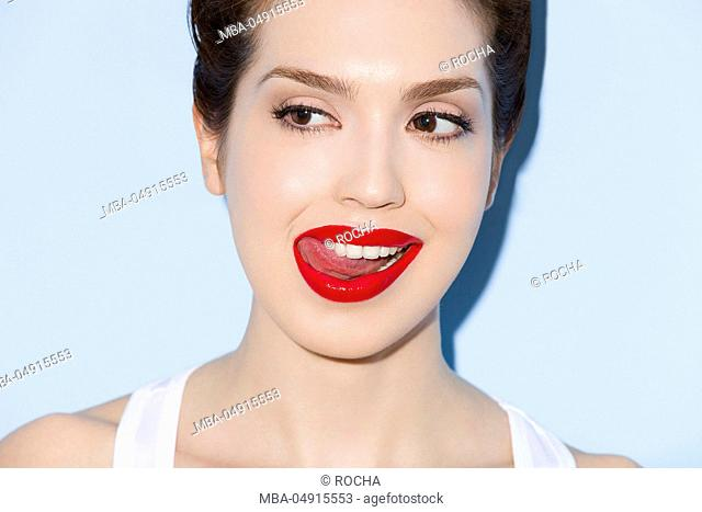 Close-up of a young woman in front of blue wall, tongue, red lips