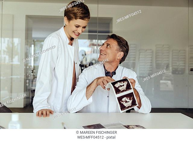 Two doctors discussing ultrasound scan of a fetus