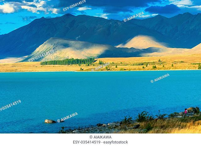 Couple sit next to turquoise lake with beautiful mountain background, Lake Tekapo, New zealand