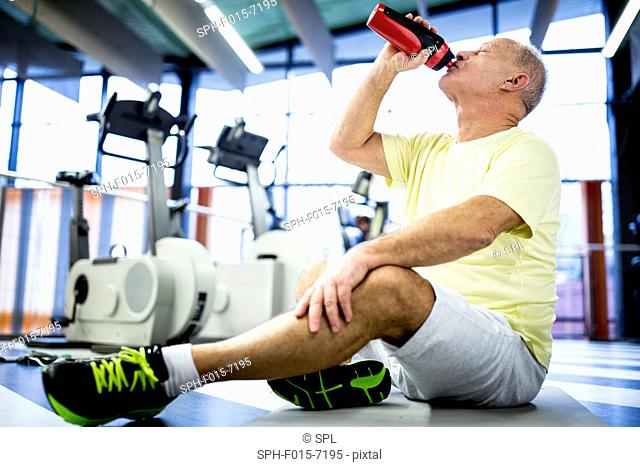 MODEL RELEASED. Senior man sitting and drinking water from water bottle in gym