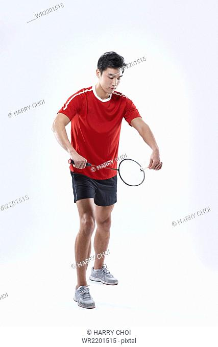 Man holding a racket and a shuttlecock looking down