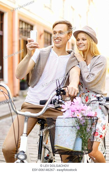 summer holidays, bikes, love, relationship, navigation, gps and dating concept - smiling couple with bicycles and smartphone in the city