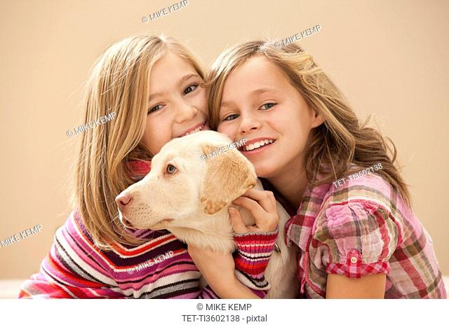 Portrait of two girls 10-11 embracing Labrador