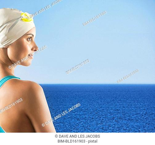 Mixed race woman wearing swimming cap on beach