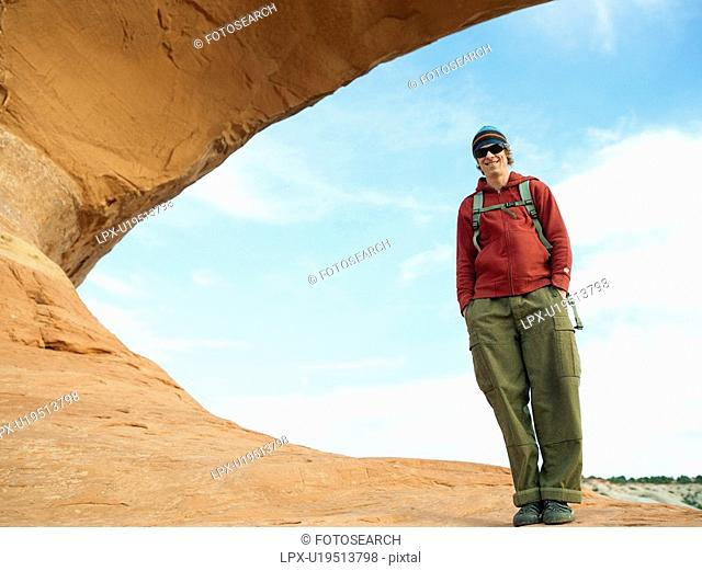 Young hiker standing on red rock, portrait, low angle view