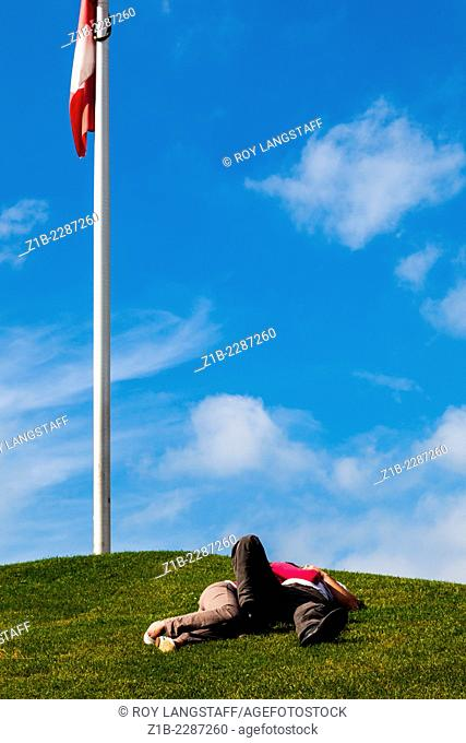 Couple relaxing on a hill by a Canadian flag, Granville Island, Vancouver