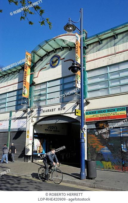 England, London, Brixton, A cyclist passing the entrance to Brixton Market Row, one of two covered arcades that together with a street market make up Brixton...