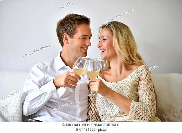 Man, woman, couple on sofa, in love, wine, glass abut