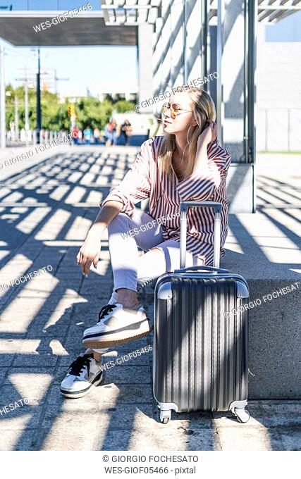 Spain, Barcelona, young woman with trolley bag waiting at station
