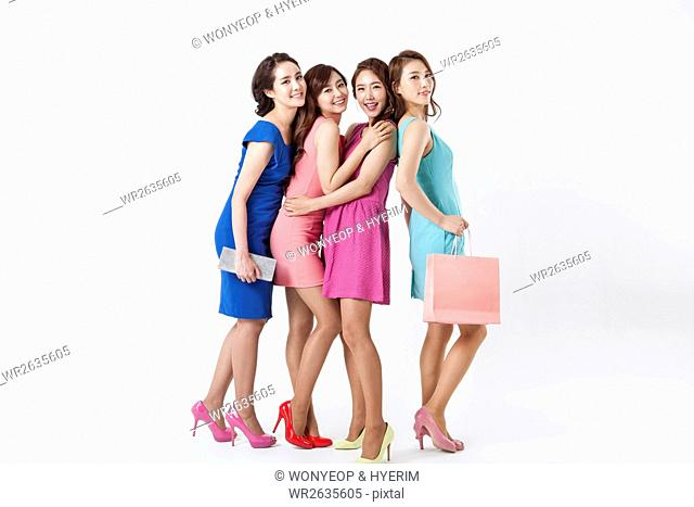 Four young smiling women in dresses posing with shopping bag