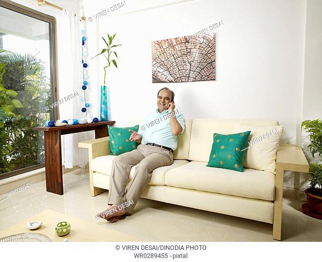 Old man talking on mobile sitting on sofa MR702T