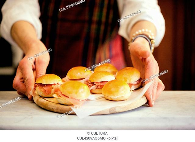 Female hands holding chopping board with prosciutto paninis