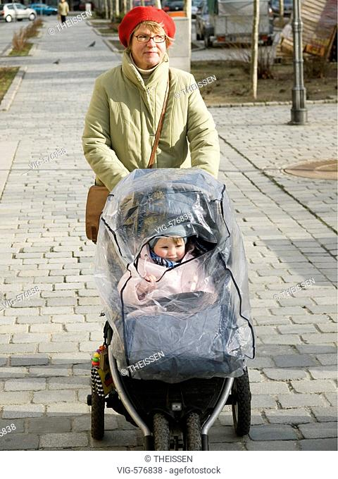 middle-aged woman with a baby in baby buggy with rain shelter. - 02/03/2007