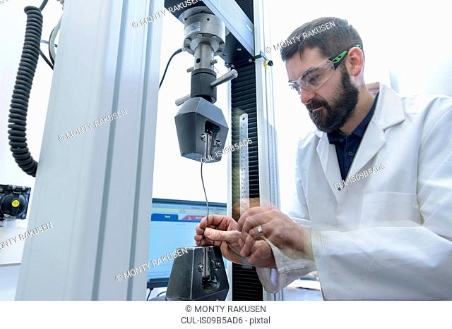 Scientist testing tensile strength of cable in laboratory