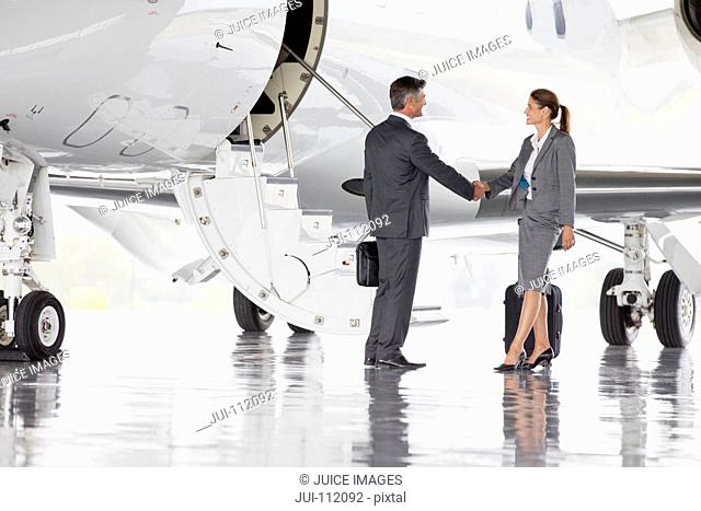 Businesswoman and Businessman shaking hands outside private jet