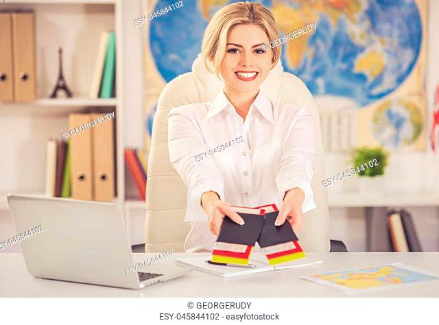 Beautiful female travel agent is offering tickets and smiling while sitting at office
