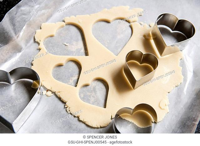 Heart-Shaped Cookie Cutters and Cookie Dough on Wax Paper