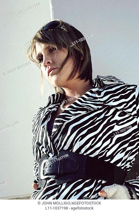 Woman in zebra coat, against white wall