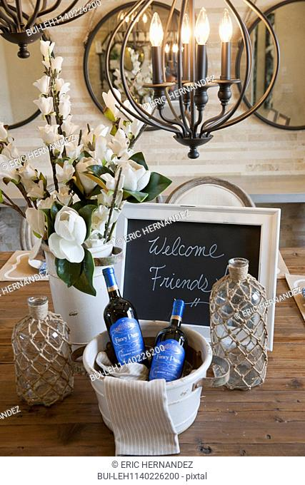 Close-up of a note 'welcome friends' with wine bottles and vase on table at home