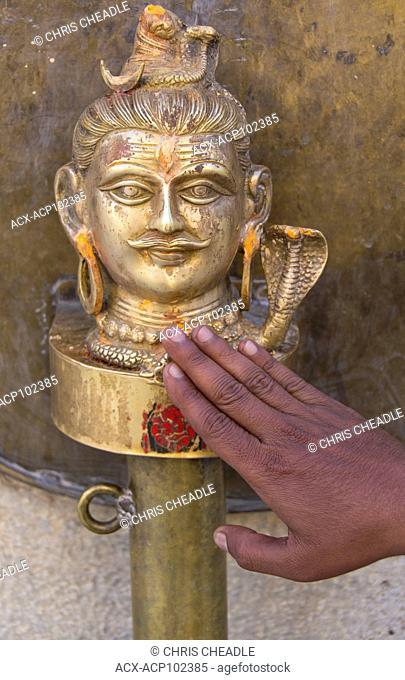 Man's hand trouches brass casting of Lord Vishnu at Jagdish Temple, Udaipur, Rajastan, India