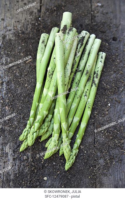 Green asparagus with soil on a wooden background