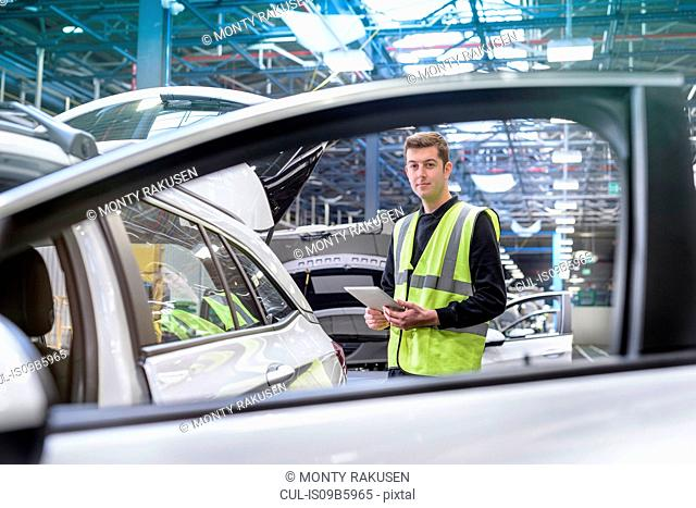 Apprentice car inspector in car factory, portrait