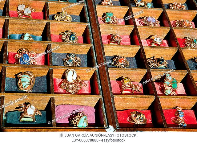 Colorful assortment of jewelry on wooden display full of rings
