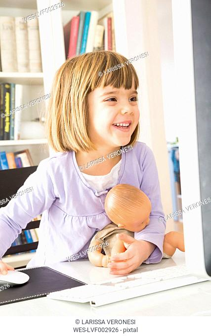 Portrait ofsmiling little girl with doll spending time at computer
