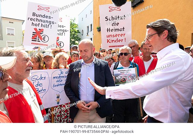 01 July 2019, Bavaria, Rosenheim: Andreas Scheuer (r, CSU), transport ministers of the federal government and Bavaria, is talking to demonstrating residents of...