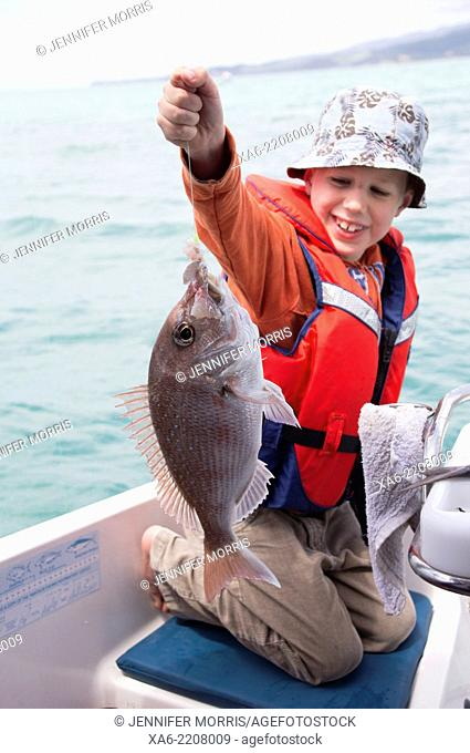A young boy who has just caught a fish