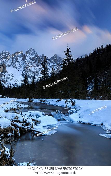 A frozen creek under a cold winter sky. Venagia Valley Panaveggio Natural Park Dolomites Trentino Alto Adige Italy Europe