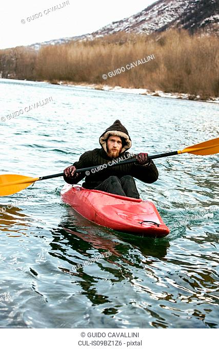 Young man kayaking on river in winter, portrait, Domodossola, Piemonte, Italy