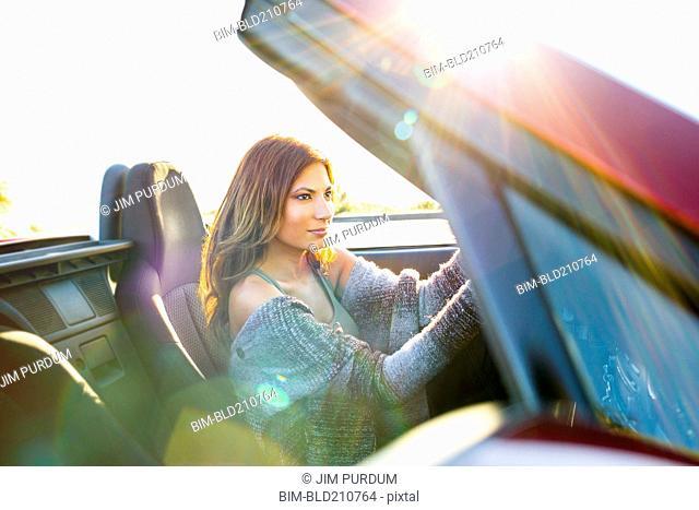 Woman driving convertible at sunset
