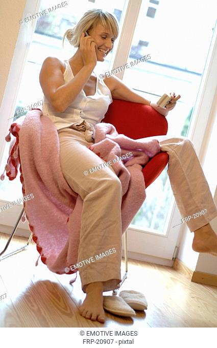 Relaxed young woman on the phone at home