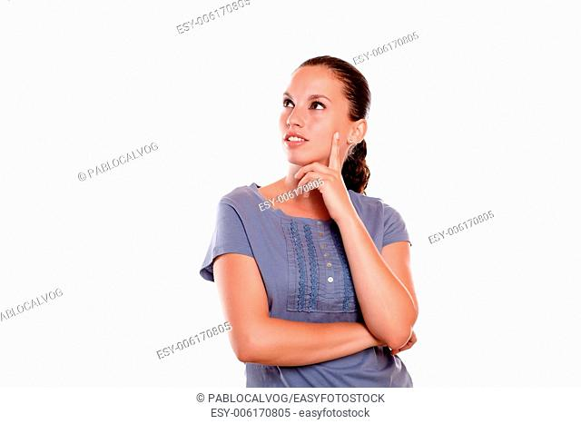 Reflective young female looking to her right up on blue blouse on isolated background - copyspace