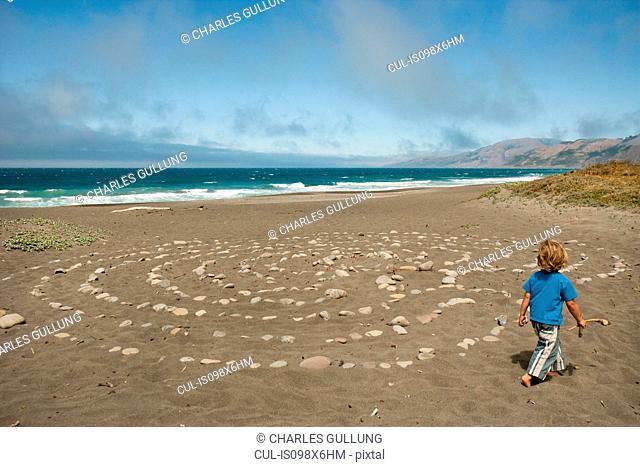 Young boy walking on beach