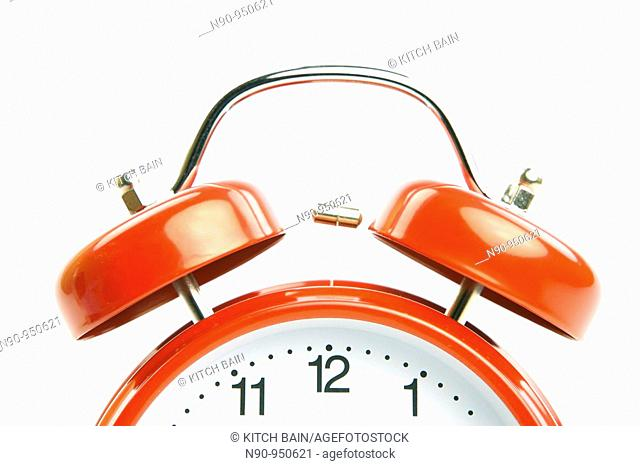 An old fahion analogue alarm clock set against a white background